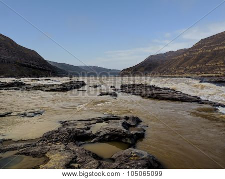 the broad and peaceful river channel of the Yellow river with eroded rocks