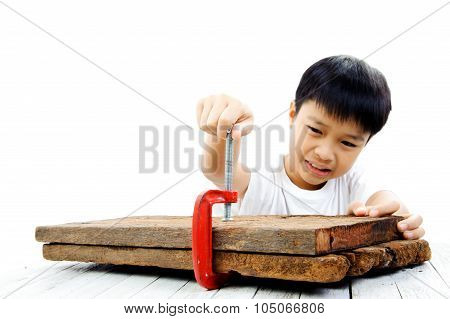 Boy Using Red Clamp To Hold Wood