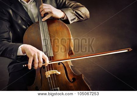 Man playing on cello on dark background