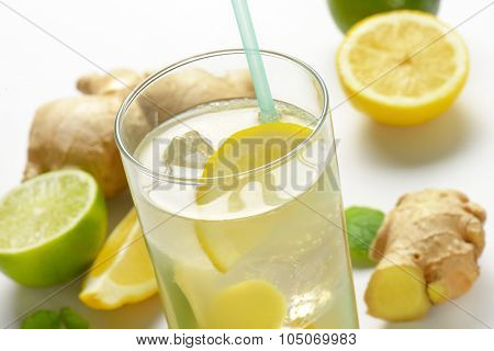 detail of glass of ginger ice tea with lemon and fresh ginger
