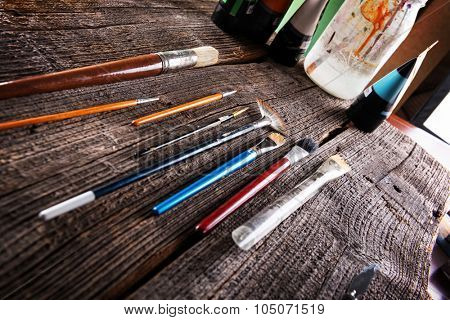 Paint brushes and paints in artist's studio