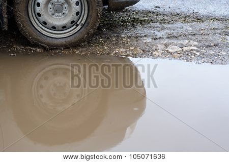 Reflection Of A Car Wheel In Puddle