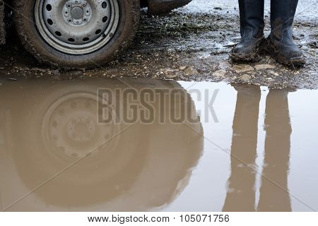Reflection Wheel Car In A Muddy Puddle And Men's Shoes