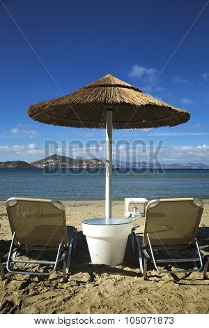 Sunbathing chairs and straw umbrella on St-Georges beach in Naxos, Greece