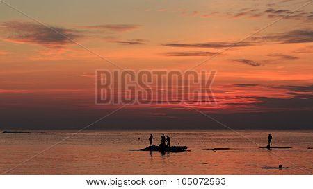 Ocean Landscape At Sunset. Silhouettes Of Fishermen.