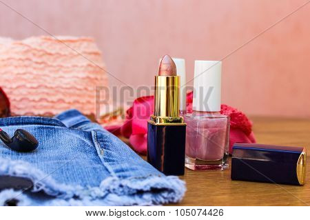 Cosmetics and women's accessories: lip gloss, nail polish, hat, denim shorts and headphones