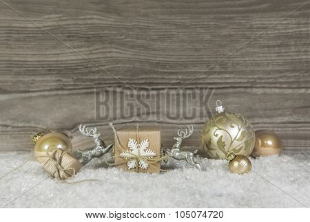 Wooden background with christmas decoration in gold, silver and white.