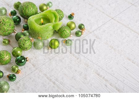 Green and white christmas background with snow, candle and balls for decoration items.