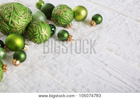 Green and white christmas background with snow and balls for decoration items.
