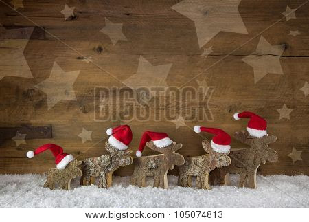 Five wooden handmade elk with red white santa hats on a background with place for text.