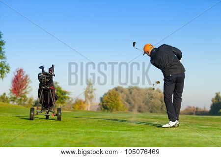 Man playing golf on green golf course. Hitting golf ball