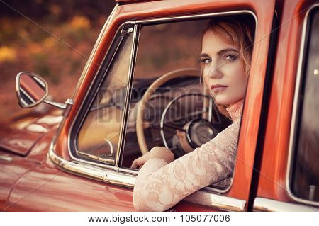 beautiful woman sitting in red retro car