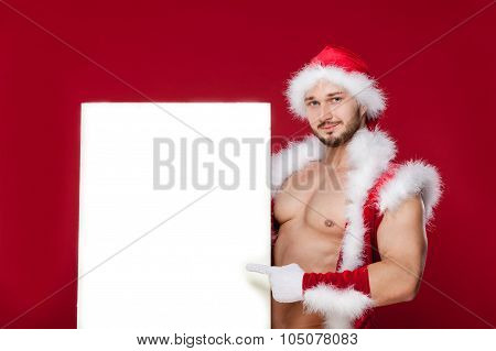 the very muscular  bronzed handsome sexy Santa Claus on red  background, hold   placard and smile, i