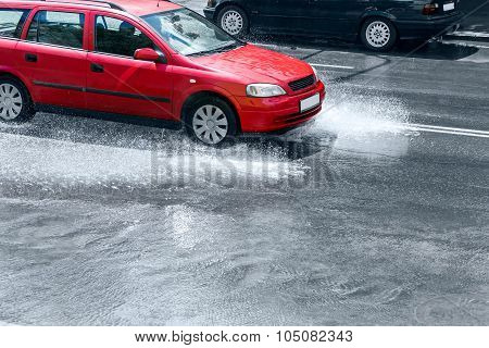 Splashing Red Car On Flooded Street