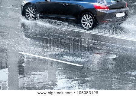 Blue Car Splashes On Flooded Road