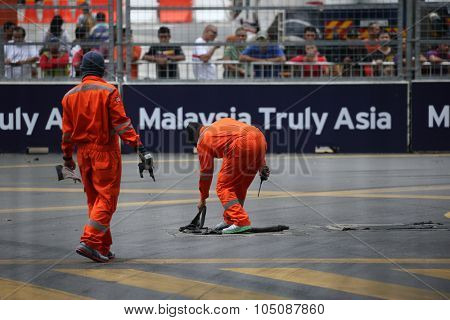 KUALA LUMPUR, MALAYSIA - AUGUST 08, 2015: Street race marshals clean the race track before the Lamborghini Blancpain Super Trofeo Race, at the 2015 Kuala Lumpur City Grand Prix.