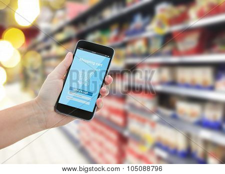 hand holding a modern smartphone in supermarket