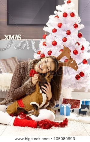 Happy woman hugging dog, sitting on floor by christmas tree.