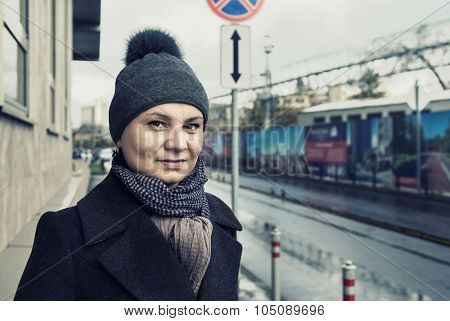 Portrait of an adult brunette woman on a city street. Real people series.