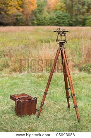 Vintage Surveyor's Level (Transit, Theodolite) with wooden Tripod and Case in a field.