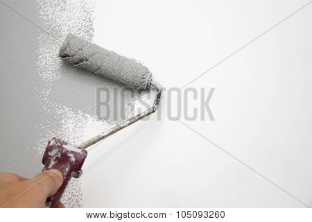 Gray Color Painting Wall With Roller In Hand