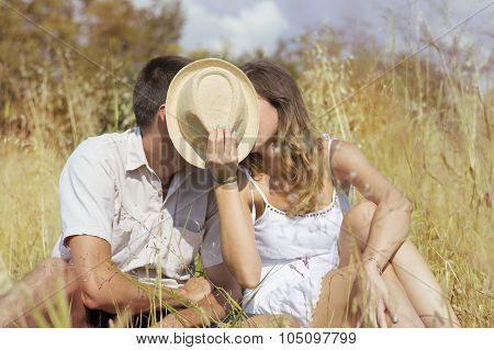 Couple Kissing In The Field Behind Hat