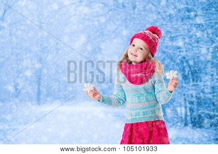 Little Girl Playing With Toy Snow Flakes In Winter Park
