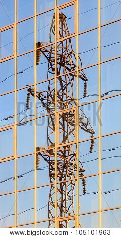 High Voltage Electric Tower Is Reflected In The Mirrored Windows Of The Building