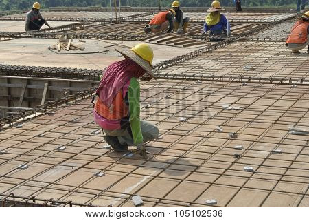 Group of construction workers fabricating floor slab reinforcement bar and formwork