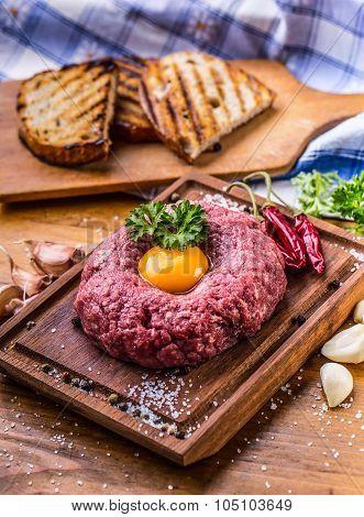 Raw beef .Tasty Steak tartare. Classic steak tartare on wooden board. Ingredients: Raw beef meat sal