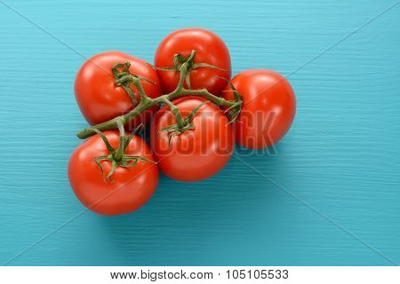 Fresh Tomatoes On The Vine On A Blue Wooden Surface