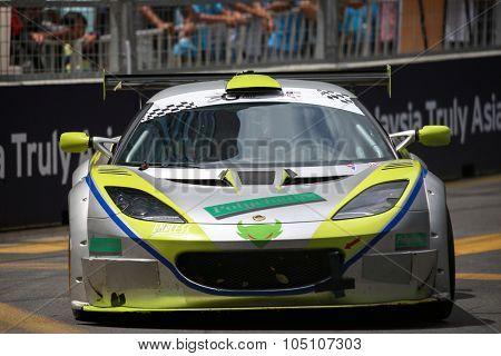 KUALA LUMPUR, MALAYSIA - AUGUST 8, 2015:  Anthony Chan drives a Lotus Evora GT4 car takes turn 2 at the inaugural 2015 Kuala Lumpur City Grand Prix.