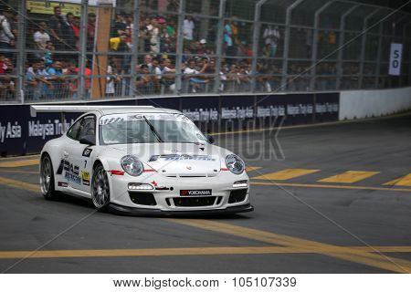 KUALA LUMPUR, MALAYSIA - AUGUST 08, 2015: Wong Kiang Kuan drives a Porsche 997 car takes turn 2 of the city streets in the KL City GT CUP Race of the 2015 Kuala Lumpur City Grand Prix.
