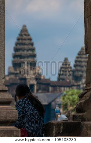 Girl from behind sitting in front of Angkor Wat