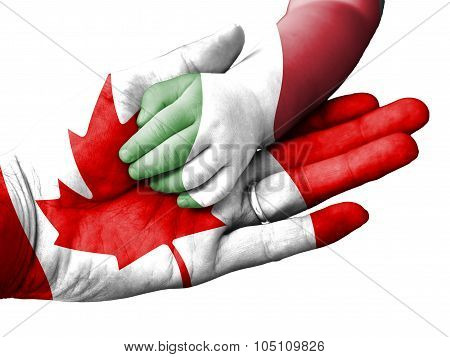 Adult Man Holding A Baby Hand With Canada And Italy Flags Overlaid. Isolated On White