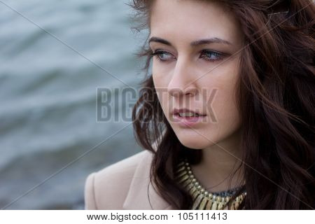 Stylish Girl In Autumn Coat Sitting By The Water