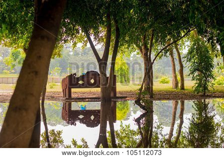 Trees with park bench reflected in pond
