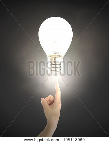 Human Index Finger Pointing At Lightbulb With Bright Light