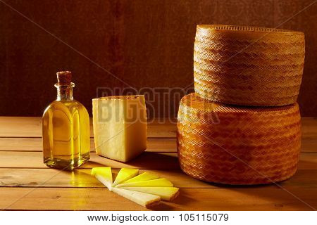 Manchego cheese from Spain in wooden table with andalusian olive oil