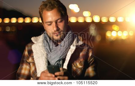 Handsome Young Man Sms Texting Using App On Smart Phone At Autum /summer Sunset In City