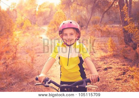 kid girl biker in mountain bike MTB at mediterranean forest