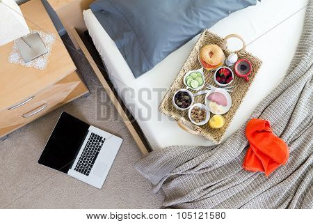 Laptop On Floor Beside Bed With Breakfast Tray