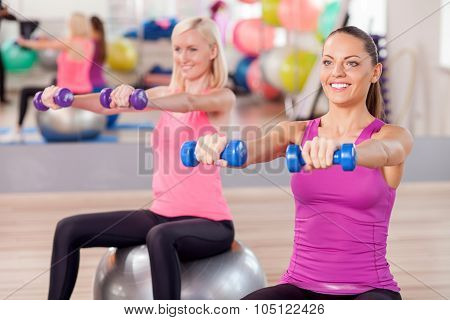 Beautiful fit girls are training with weights