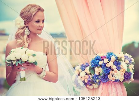 Beautiful blonde bride with a bouquet of flowers near wedding arch with flowers and chiffon