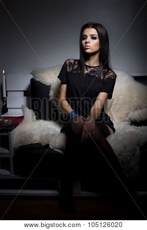 beautiful young sexy girl with full lips sitting on the sofa covered with white fur in a black littl