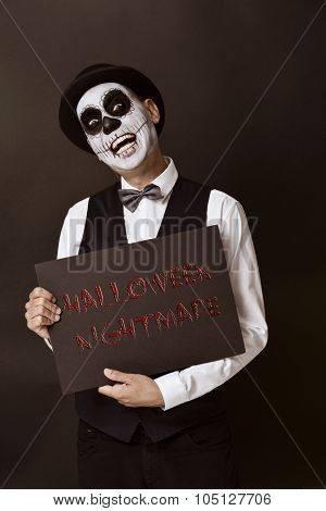 a man with calaveras makeup, wearing bow tie and bowler hat, shows a black signboard with the text halloween nightmare written in it