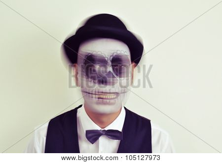 portrait of a man with calaveras makeup, wearing bow tie and bowler hat, in motion