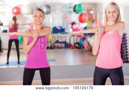 Cheerful ladies are exercising in fitness center