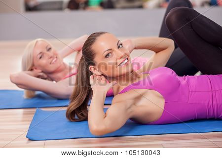 Pretty fit girls are exercising in gym