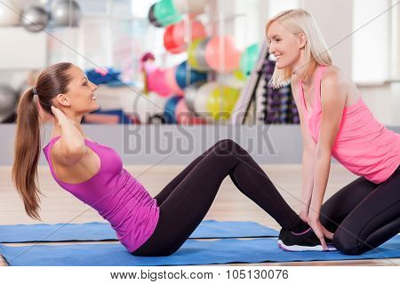 Cheerful young women are training in fitness center